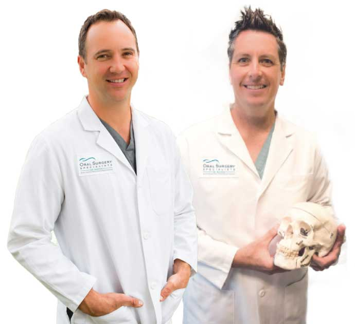 Two doctors smiling and holding a human skull.